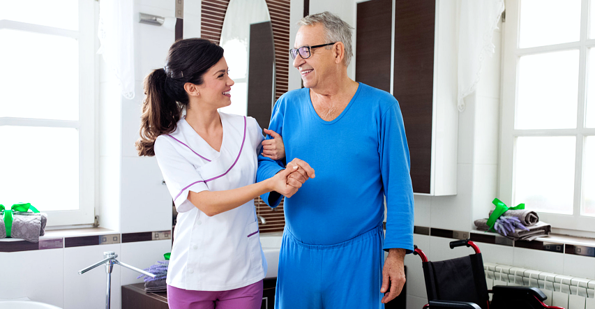 A caregiver and elderly standing and smiling