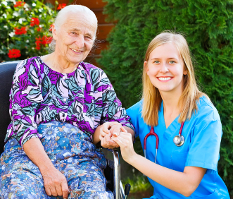 caregiver and elderly smiling while sitting