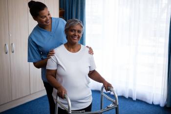 Nurse assisting senior woman in walking with walker